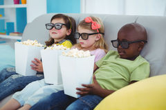 Happy kids sitting together with boxes of popcorn Royalty Free Stock Image