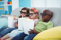 Happy kids sitting together with boxes of popcorn Stock Photo