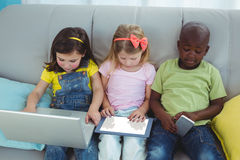 Happy kids sitting together with a tablet Royalty Free Stock Images