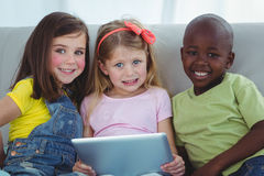 Happy kids sitting together with a tablet Stock Image