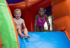 Happy kids sliding down an inflatable bounce house. Cute smiling little girl and boy playing on an inflatable  bounce house outdoors. Having fun playing on a Royalty Free Stock Photos