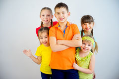 Happy kids smiling. Group of cheerful kids is standing in multicolored t-shirts and smiling Stock Photography