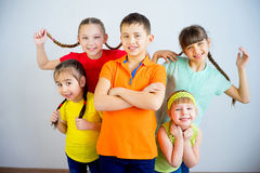 Happy kids smiling. Group of cheerful kids is standing in multicolored t-shirts and smiling Stock Photo
