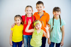 Happy kids smiling. Group of kids is standing in multicolored t-shirts and smiling Stock Photo