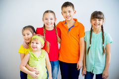 Happy kids smiling. Group of kids is standing in multicolored t-shirts and smiling Stock Photography