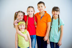 Happy kids smiling. Several kids are standing in multicolored t-shirts and smiling Royalty Free Stock Photography