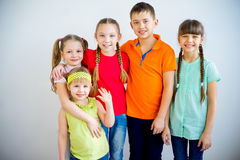 Happy kids smiling. Several kids are standing in multicolored t-shirts and smiling Stock Photography