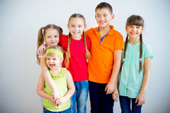 Happy kids smiling. Several kids are standing in multicolored t-shirts and smiling Royalty Free Stock Photo