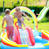 Happy kids splashing in inflatable garden pool Stock Photo