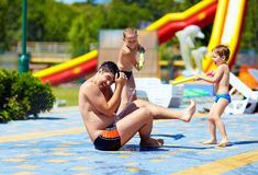 Happy kids splashing the water on father in aquapark Royalty Free Stock Photography