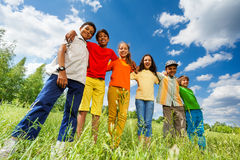 Happy kids stand in row straight and hug Stock Image