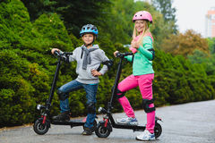 Happy kids standing on electric scooter outdoor.  stock photography