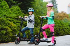 Happy kids standing on electric scooter outdoor.  royalty free stock photo