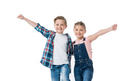 Happy kids standing embracing with raised hands and smiling at camera Stock Image