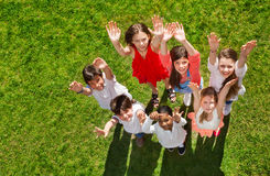 Happy kids standing on grass and waving hands royalty free stock photo