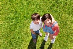 Happy kids standing on the green lawn and hugging Royalty Free Stock Photos
