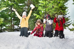 Happy kids standing on knees at sunny winter day Stock Images
