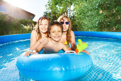 Happy Kids Swimming In The Pool With Rubber Ring Stock Photos