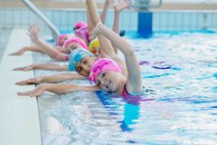 Happy kids at the swimming pool. young and successful swimmers pose. stock images