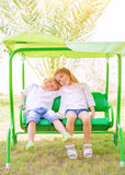 Happy kids on the swing. Portrait of two happy kids on swing, enjoying entertainment in summer camp, carefree childhood, active lifestyle, friendly family Royalty Free Stock Image