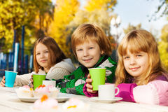 Happy kids with tea cups sitting outside Royalty Free Stock Image