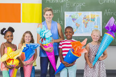 Happy kids and teacher holding gifts in classroom stock images