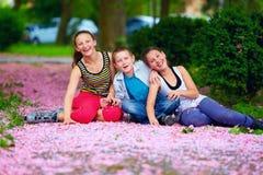 Happy kids, teenagers having fun in blooming park Royalty Free Stock Photos