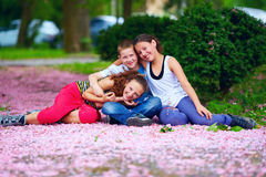 Happy kids, teenagers having fun in blooming park Royalty Free Stock Images