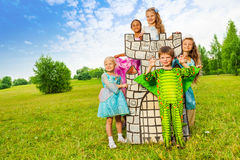 Happy kids in theatric costumes play around tower. Happy kids in theatric costumes play around drawn tower and having fun Stock Images