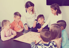 Happy kids thinking at table with board game royalty free stock photo