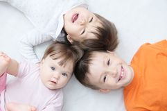 Happy kids, three laughing children different ages lying, portrait of boy, little girl and baby girl, happiness in childhood Royalty Free Stock Images