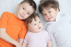 Happy kids, three laughing children different ages lying, portrait of boy, little girl and baby girl, happiness in childhood. Of siblings, living in big family Royalty Free Stock Photography