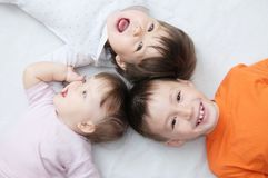 Happy kids, three laughing children different ages lying, portrait of boy, little girl and baby girl, happiness in childhood. Of siblings, living in big family Royalty Free Stock Photo