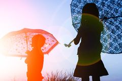 Happy Kids with an umbrella silhouette on nature in the park sunset stock photography
