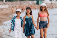 Happy kids walking together through the water royalty free stock photography