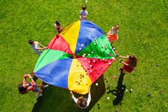 Happy kids waving rainbow parachute full of balls. Top view picture of kids standing in a circle on the green lawn and holding rainbow parachute full of colorful stock image