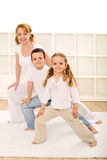 Happy kids and woman doing gym exercises Stock Photo