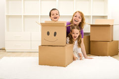 Happy kids and woman having fun in their new home stock images