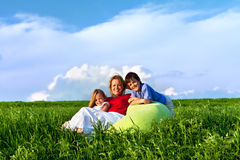 Happy kids and woman sitting outdoors Royalty Free Stock Photos