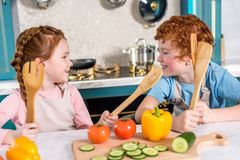 Happy kids with wooden utensils smiling each other while cooking together. In kitchen royalty free stock photos