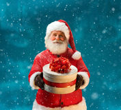 Happy and kind Santa Claus with christmas present. And looking at camera / Merry Christmas & New Year's Eve concept / Closeup on blurred blue background Royalty Free Stock Photos
