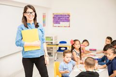 Happy kindergarten teacher in a classroom. Portrait of a cute Hispanic kindergarten teacher standing in a classroom full of students royalty free stock photos