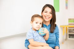 Happy kindergarten teacher at work. Portrait of a beautiful Hispanic kindergarten teacher having fun with a little boy in the classroom Stock Image