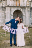 Happy kissing bride and groom holding artistic papercut love letters Stock Photo