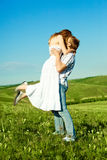 Happy kissing couple. Happy young loving couple kissing outdoor in summertime Royalty Free Stock Photo