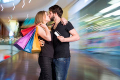 Happy kissing couple with shopping bags Stock Photography