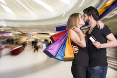 Happy kissing couple with shopping bags in the mall Royalty Free Stock Images
