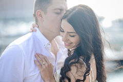 Happy kissing loving couple on sunny outdoors background Royalty Free Stock Photography