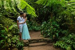 Happy kissing multiracial couple hugging on walking trail in tropical forest. Young mixed race couple on vacation in Asia. Ubud, stock photo