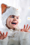 Happy kitten. Little girl wearing a white kitten costume licking her fingers Royalty Free Stock Photography